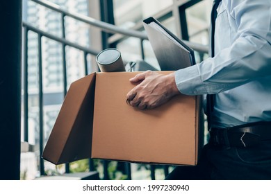 Unemployed hold cardboard box and laptop bag, dossier and drawing tube in box. Quitting a job, businessman fired or leave a job concept. - Shutterstock ID 1997230940
