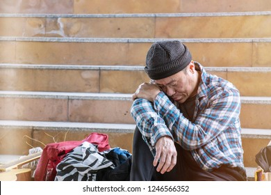 Unemployed homeless man is sadly sitting by the stairs.