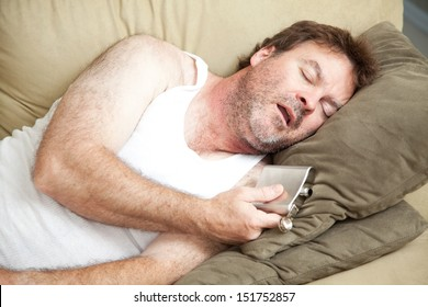 Unemployed man passed out drunk on the couch with a flask of booze in his hand.