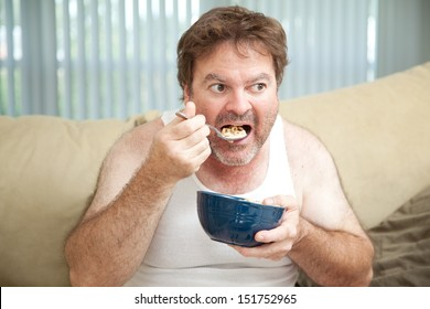 Unemployed man sitting on the couch eating cereal as he watches television.