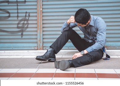 Unemployed man sitting on the street. Asia man looking stress and emotional with closed store background.