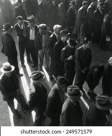 Unemployed men wait in line to file Social Security benefit claims. In January 1938, new Social Security programs made unemployment compensation available. California, by Dorothea Lange.