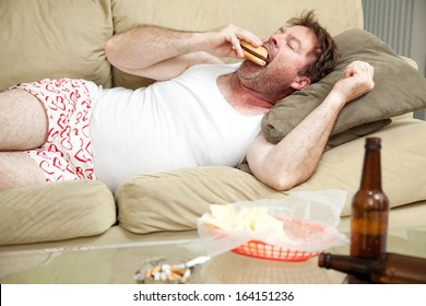Unemployed middle aged man at home on the couch in his underwear, eating a hamburger,  with a marijuana joint in the ashtray and beer bottles lying around.