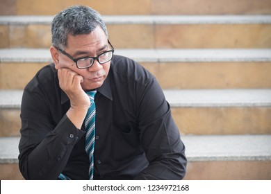unemployed old asian business man. portrait of businessman suffering from layoff, economic recession, business crisis, unemployment, bankruptcy or business depression. asian 50s old man model.