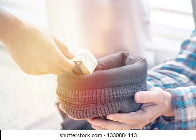 Unemployed people is begging for money. Someone is giving 20 U.S.D. to his beanie hat. Hand is giving 20 dollars note to beggar.