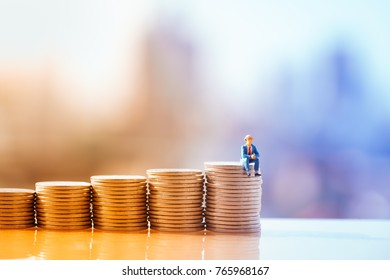 Unemployed people crisis, Stress and Jobless. Miniature people: Small businessman sitting on top step of coin stack, unemployment, fired from job, disappointed, loss and feeling down concept.