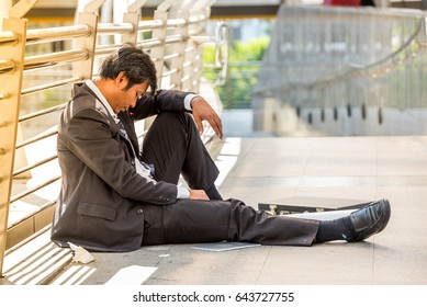 unemployed Sad fired  dismissed Desperate businessman sit and looking for a job on street