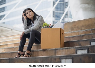 Unemployed stressed office people sitting outside office with her box of office properties. She was dismissed from business downsizing. Failure and layoff concept