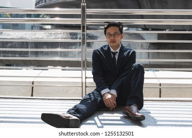 Unemployed stressed young Asian business man sitting on floor outdoors. Failure and layoff concept.