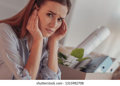 Unemployed woman. Portrait of young distressed worker touching her temples and expressing sadness in her eyes after being dismissed from a job