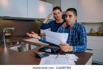Unemployed young couple with many debts reviewing their bank accounts. Financial family problems concept.