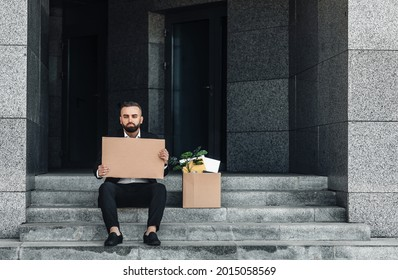 Unemployment concept. Depressed mature businessman sitting with empty poster cardboard sign and box of personal belongings on stairs near office center, got fired, free space