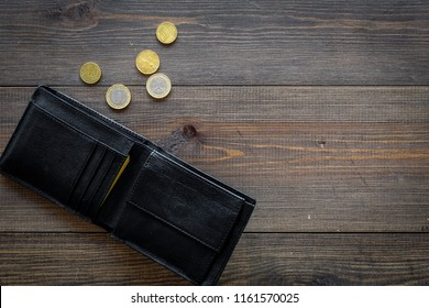 Unemployment concept. Lack of money. Coins fall out of wallet on dark wooden background top view copy space