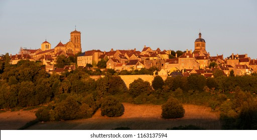 The UNESCO village of Vezelay on a hill with the Benedictine abbey and church of Saint Mary Magdalene at sunset in Yonne, France.