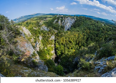 Unesco world heritage site Skocjanske jame taken with a wide fish eye view. Looking towards the deep gorge with cave entrance and walking paths. Village of Skocjan in the background.