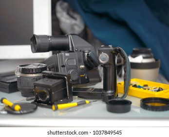 Uneven focus shot of a messy table with a photo gear needs repair