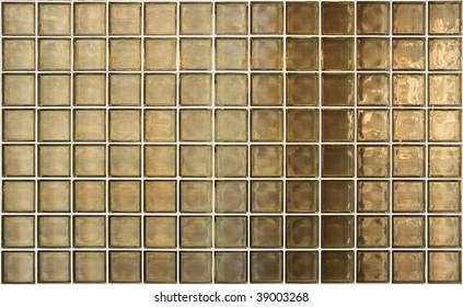 Uneven golden light reflects through glass block wall