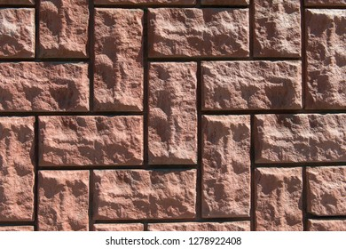 Uneven rough red bricks with asymmetrical masonry. Closeup stone background.