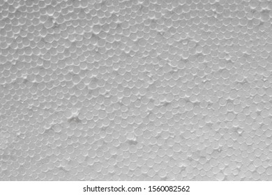 Uneven texture of plastic foam . White styrofoam board. Closeup. Polystyrene sheet surface. Abstract circles background