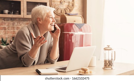 Unexpected Call. Surpised Aged Woman Talking On Cellphone In Kitchen And Emotionally Gesturing