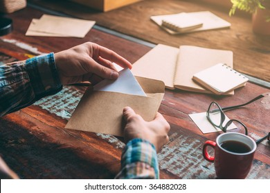 Unexpected letter. Close-up image of man opening an envelope while sitting at the rustic wooden table