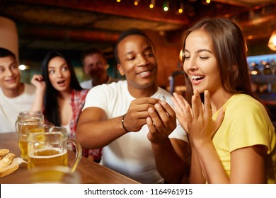 Unexpected marriage proposal in bar with company of friend on background. Man in love proposing girlfriend to marry him, holding wedding engagement ring, girl looking at it, all around confusing.
