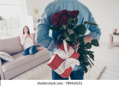 Unexpected moment in routine everyday life! Cropped photo of man's hands hiding holding chic bouquet of red roses and gift with white ribbon behind back, happy woman is on blurred background