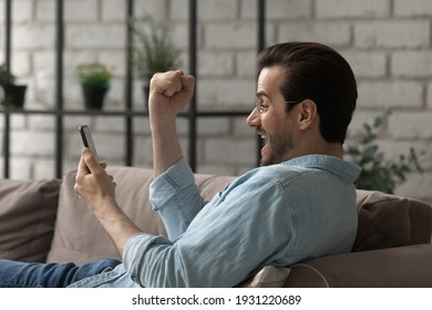 Unexpected reward. Happy overjoyed millennial man in glasses rest on couch looking at cell screen scream shout yes in euphoria becoming app game winner. Shocked excited funny guy win great money prize
