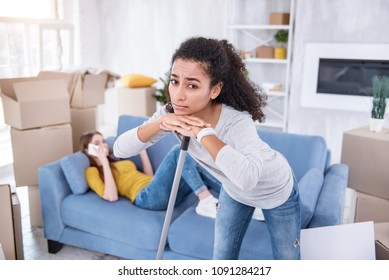 Unfair life. Pretty curly girl cleaning the floor in the new apartment while her roommate lying on the sofa and doing nothing but talking on the phone