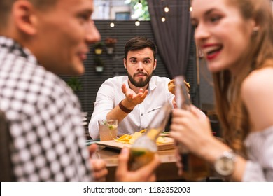 Unfair situation. Sad young man feeling awkward while eating a burger and looking at his friends talking