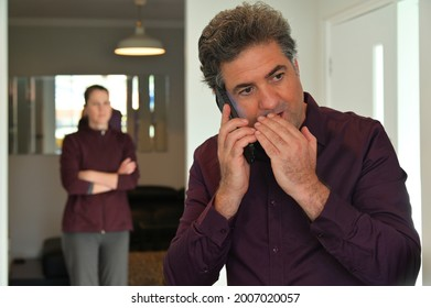 Unfaithful husband, Mature adult man (male age 40-45) talking on mobile phone with his lover while his jealous suspicious wife watching and listening to conversation from behind.Trust issues concept