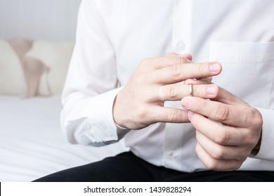 Unfaithful man taking off his wedding ring, man sitting on the bed in the hotel, his mistress's underwear in the background, closeup, cropped image, toned. The concept of infidelity in marriage