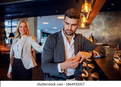 Unfaithful middle-aged man sitting in the bar of a fancy hotel and taking off his wedding ring. In the background is a woman who is seducing him.