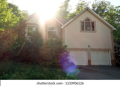 Unfinished abandoned model home, backlit by the sun. Bright sun glare visible.