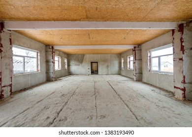 Unfinished apartment or house big loft room under reconstruction. Plywood ceiling, plastered walls, window openings, cement floor. Construction and renovation concept.
