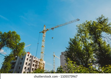 Unfinished building construction and building cranes against blue sky background. Destruction of nature and deforestation for the construction of new areas. Concept of urban development.
