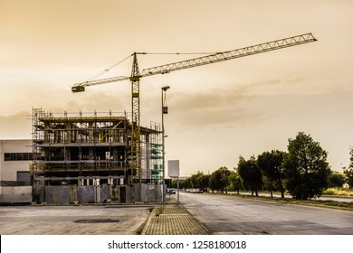 an unfinished building at dusk with a yellow crane near it