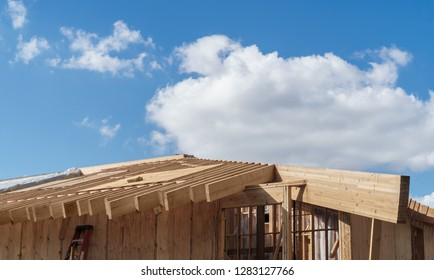 Unfinished building, new wood frame construction. Blue sky, clouds. Room for text.