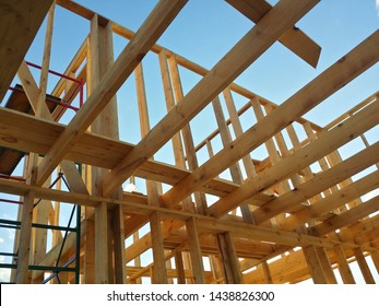 Unfinished construction of wooden house with metal ladder against blue sky. Close-up of ceiling frame.