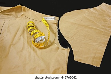 Unfinished costume and short sleeve with tape measure on black background - Costume sewing background.