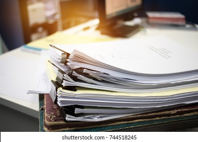 Unfinished documents stacks of paper files on office desk for report papers,piles of unfinished papers sheet achieves with clips indoor, Business offices concept.Document is  written, drawn,presented.