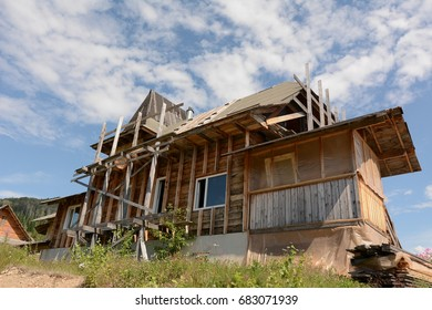 unfinished house with wooden beams from the scaffolding on the hill against the blue sky and white clouds