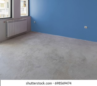Unfinished interior of apartment  under construction with gray concrete floor, windows and color wall
