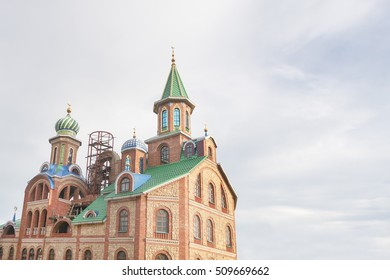Unfinished Mosque of red bricks with green dome and golden spire