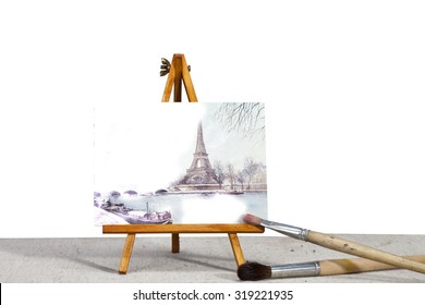 The unfinished painting of the Eiffel Tower on a small wooden easel.