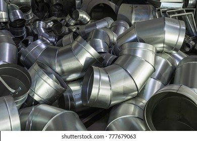 Unfinished parts for stainless steel industrial ventilation system during production. Metal pipes, industrial abstract background, toned