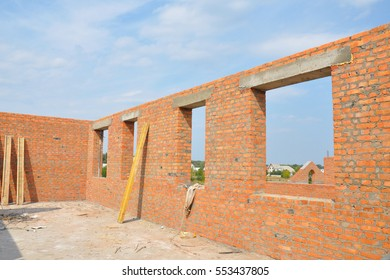 Unfinished Red Brick House Wall  under Construction without Roofing.  Attic Windows Concrete Lintel Frame Construction. House construction site. Brickwork.