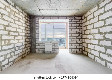 The unfinished room in a residential building under construction with the window, the balcony and the bare walls. The use of aerated concrete blocks in high-rise building construction.