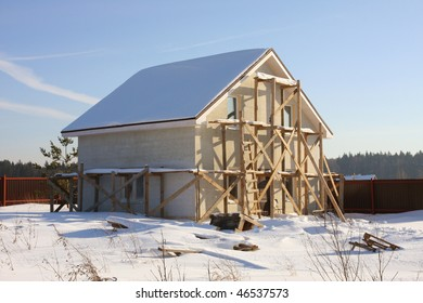 An unfinished suburban house. Winter sunny day.