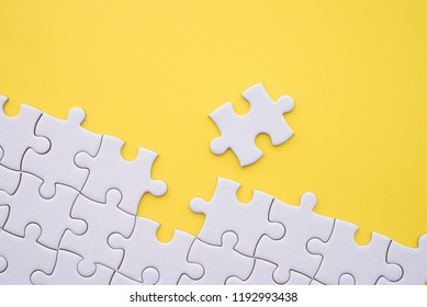 Unfinished white jigsaw puzzle on yellow background with copy space. Business strategy teamwork and problem solving concept. Teamwork is collaborative effort of team to achieve goal or complete task.